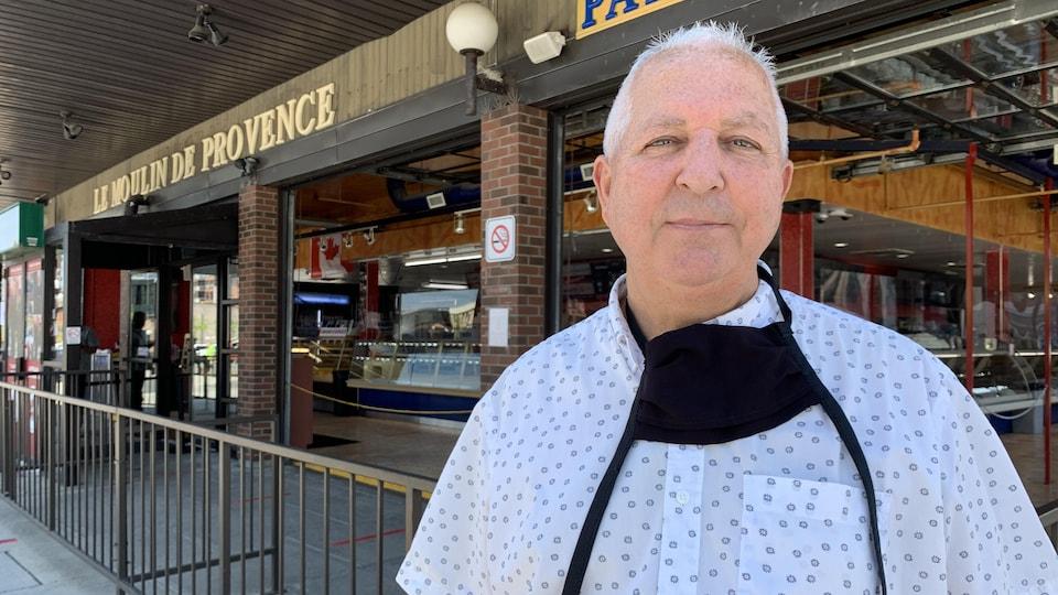 L'homme devant son restaurant.