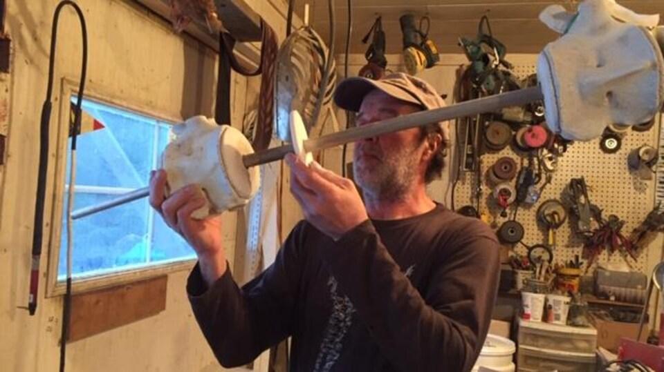 Claude Bourque assemble deux os du squelette du petit rorqual dans son atelier.