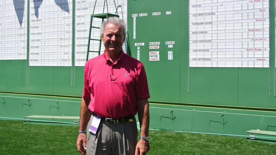 Un homme pose devant un tableau de résultat au golf.