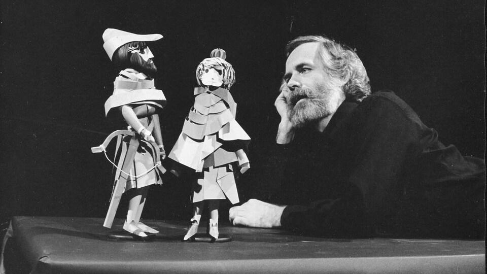 Claude Lafortune regardant deux personnages en papier.