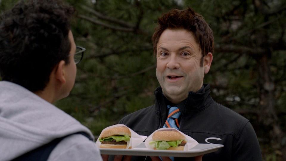 L'homme rit en tenant un plateau qui contient deux hamburgers.