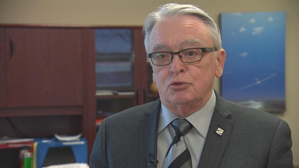 Homme aux cheveux gris portant des lunettes, chemise, cravate et veston en entrevue à la télé.