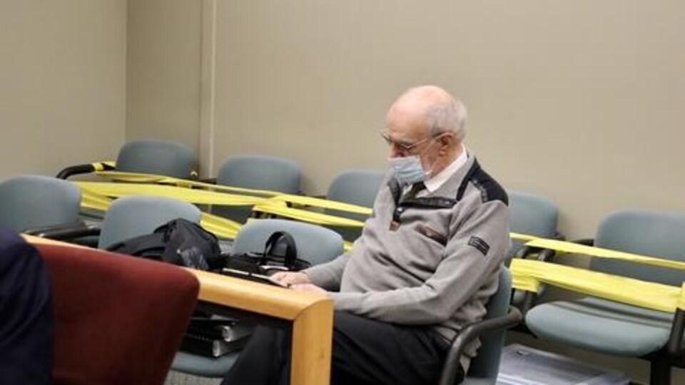Un homme âgé portant des lunettes assis sur une chaise.
