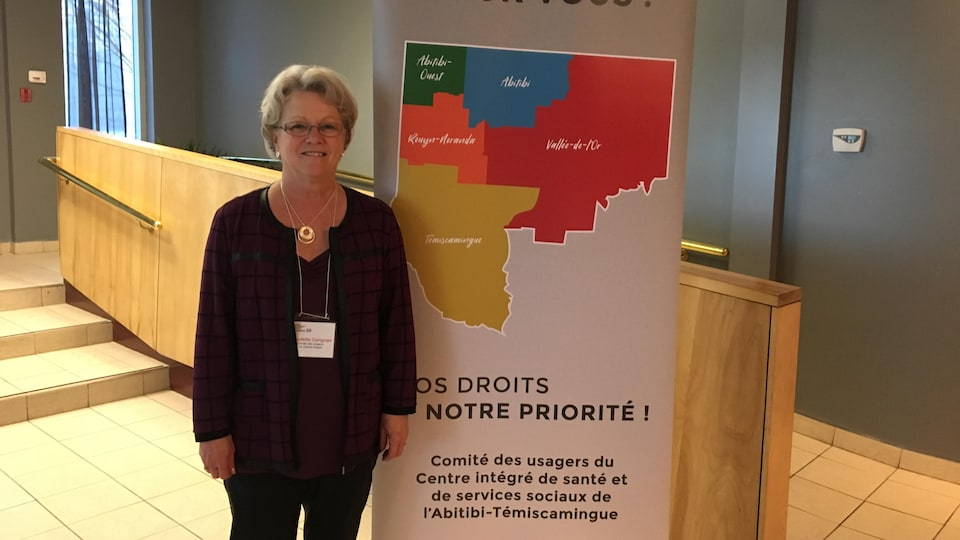 Une femme pose devant une affiche du Comité des usagers du Centre intégré de santé et de services sociaux de l'Abitibi-Témiscamingue.