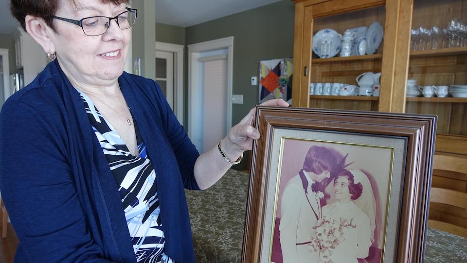 Une dame qui tient une photo dans un cadre. À la photo, on voit un couple en habillement de mariage.