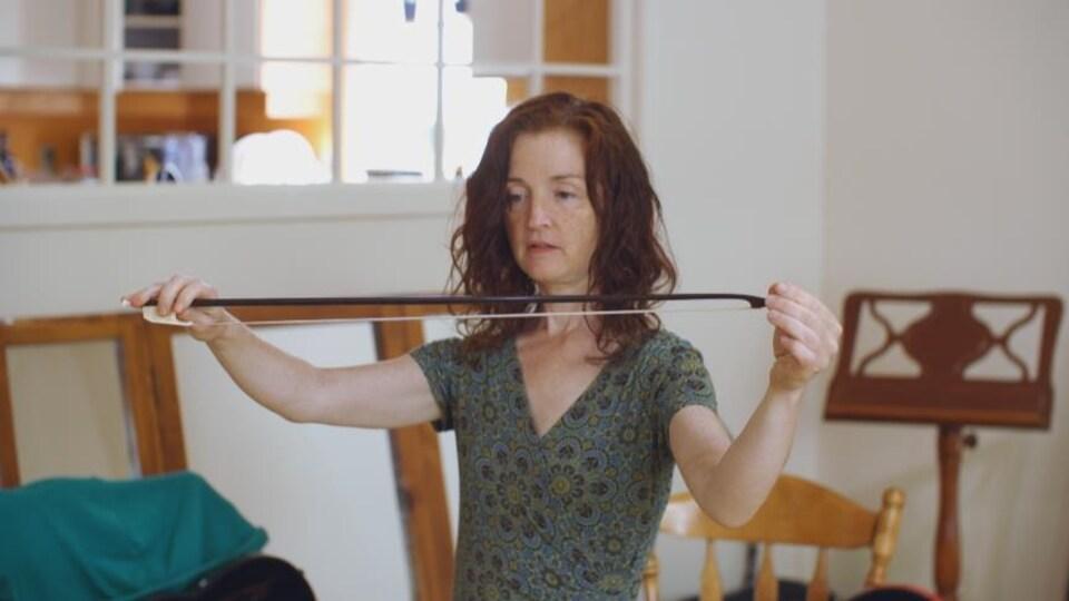 Une femme, Claudine St-Arnaud, tient entre ses mains l'archet de son violon, qu'elle montre au photographe.