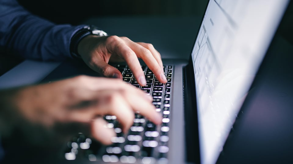 Gros plan de mains sur un clavier d'ordinateur portable.