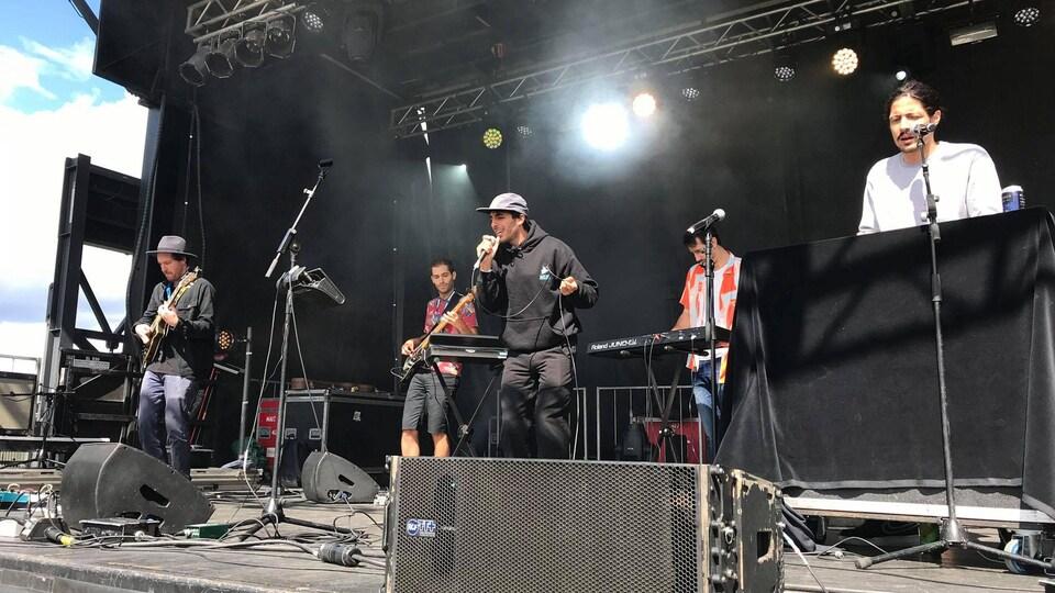 Les 5 membres de la formation jouent de la musique sur une scène extérieure et un ciel ensoleillé.
