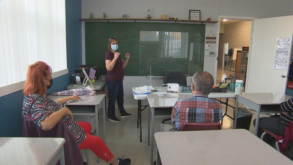Des adultes sont assis à des pupitres, dans une classe, et suivent un cours avec une formatrice.