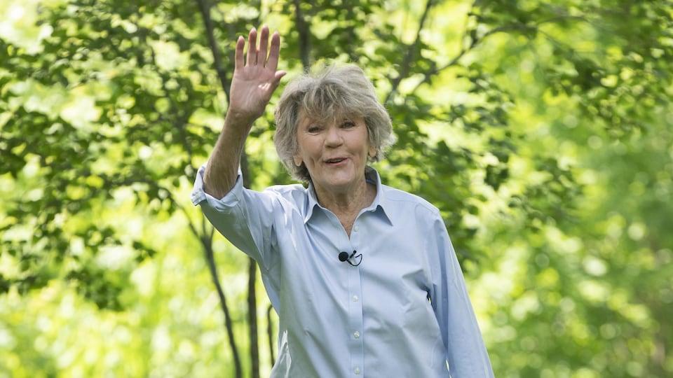 Clémence DesRochers, debout à la campagne, nous envoie la main.