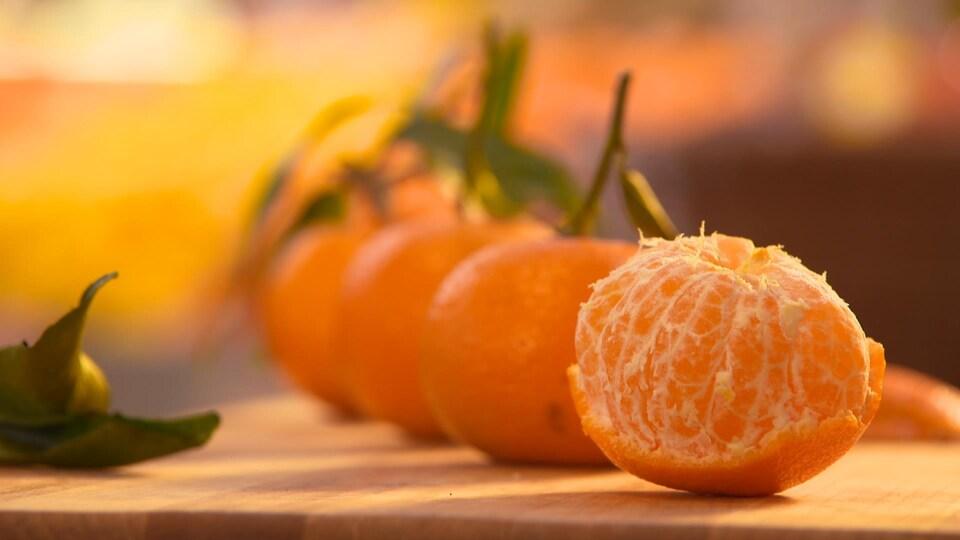 Des clémentines sur une table avec en avant-plan, un fruit dont la pelure a été enlevée.