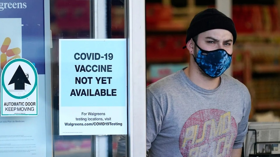 A customer wearing a mask comes out of a pharmacy.