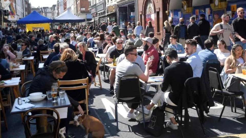 Des personnes mangent et boivent dehors dans le quartier de Soho à Londres.
