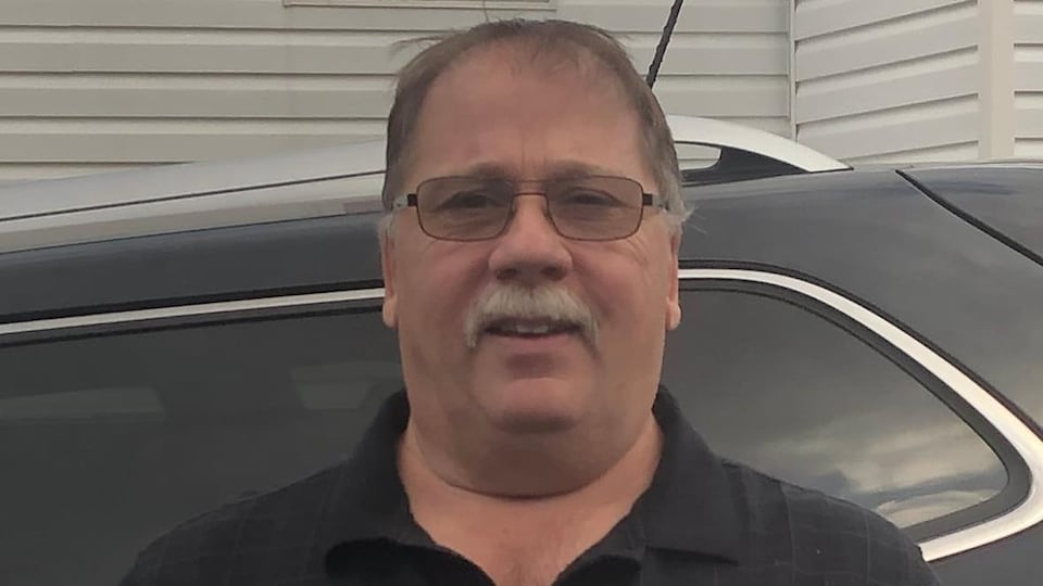 Un homme en polo noir avec des lunettes et une moustache grise.