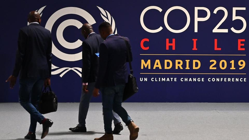 Des hommes marchent devant un panneau qui indique le site de la COP25 à Madrid