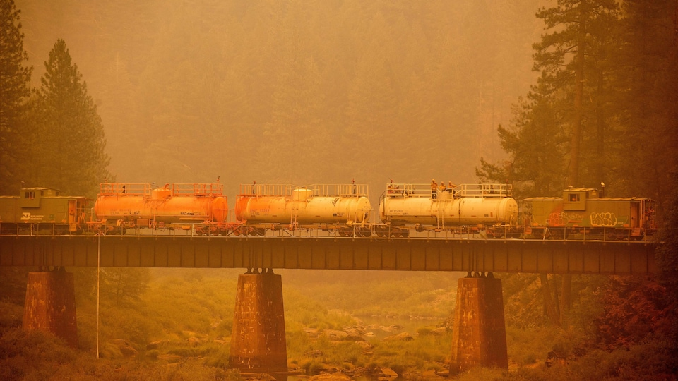 A train of firefighters crossing a bridge over terrain occupied by firefighters.