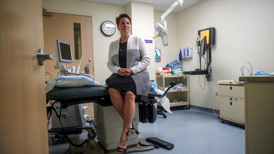 La docteure Colleen McNicholas est assise sur une table de travail dans une salle de traitement de la clinique.