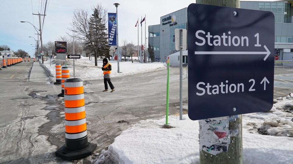 Des panneaux indiquent les endroits où se rendre et une personne est prête, près de cônes, pour diriger les gens vers le lieu approprié.