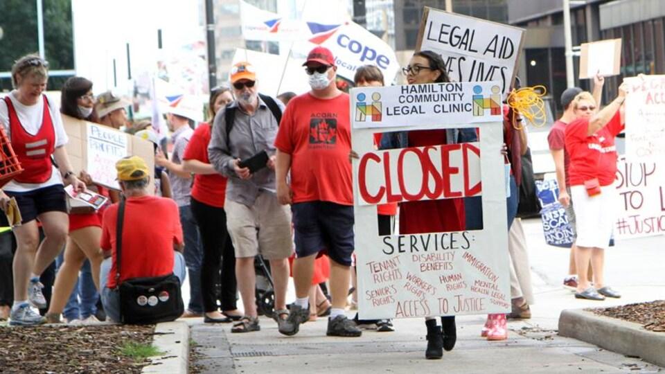 Des manifestants tiennent des pancartes sur un trottoir.