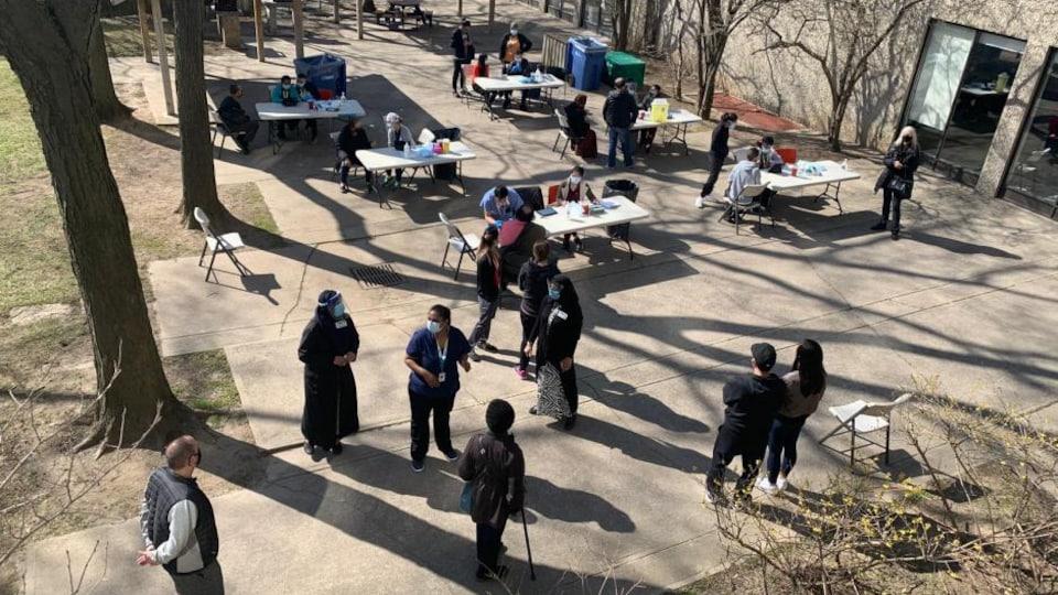Des gens attendent debout à l'extérieur d'une tour d'habitation, tandis que d'autres se font vacciner assis près d'une table pliante.