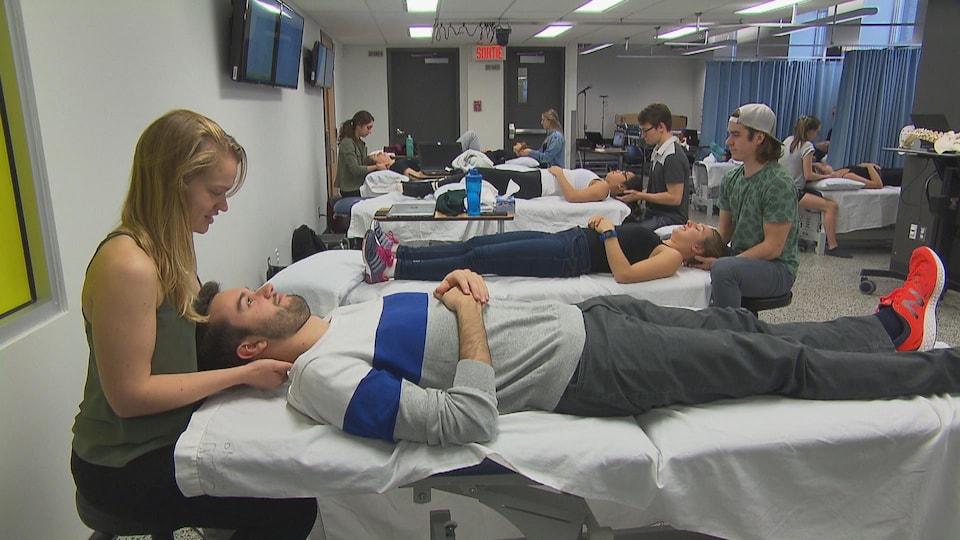 Des étudiants sont en train de traiter leur patient couché sur un lit.