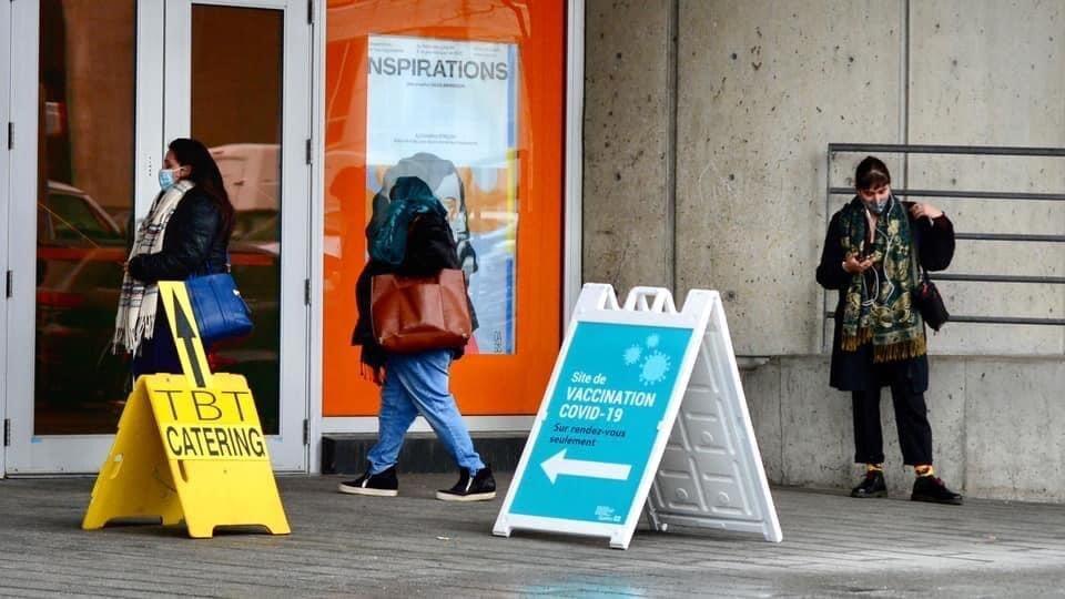 Des gens attendent devant un site de vaccination, à Montréal.