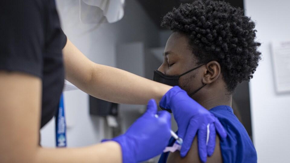 Un homme reçoit une injection de vaccin dans le bras.