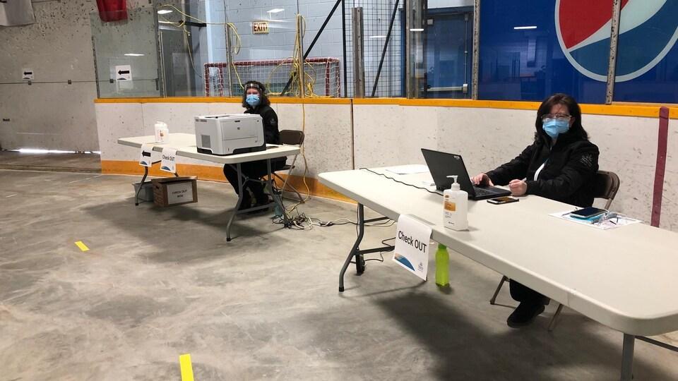 Deux personnes sont assises à deux bureaux.