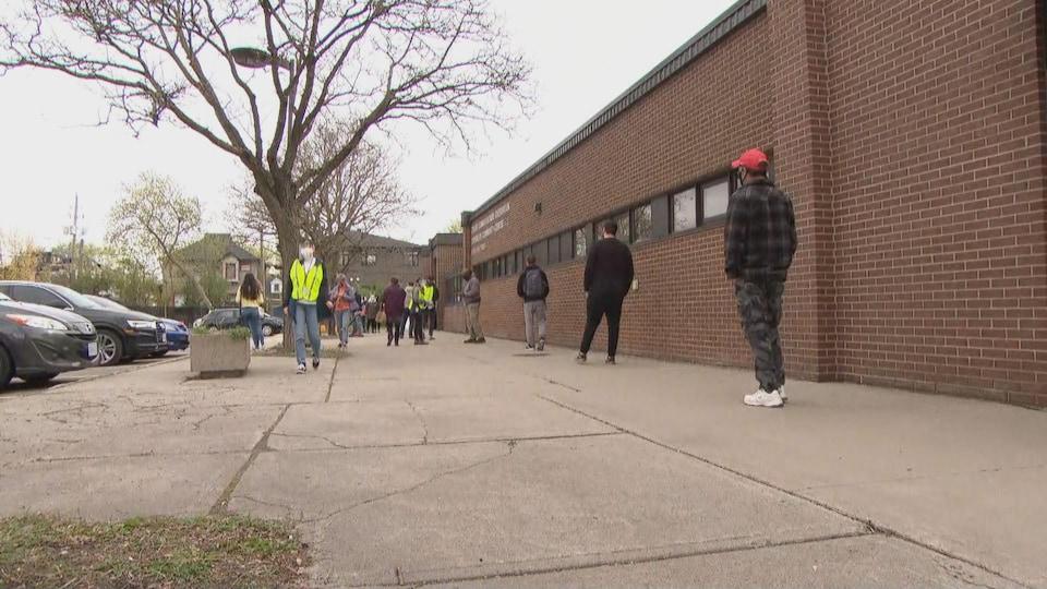 Des gens font la file, à deux mètres, devant le centre communautaire d'Overbrook.