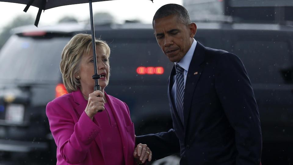 Hillary Clinton et Barack Obama réunis sous un parapluie.