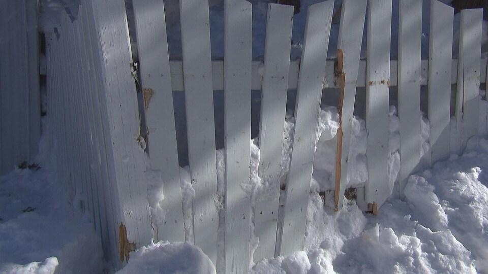 Une clôture blanche abîmée par les opérations de déneigement.