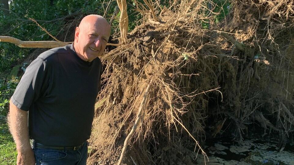 Clément Ladouceur devant les racines d'un arbre déraciné.