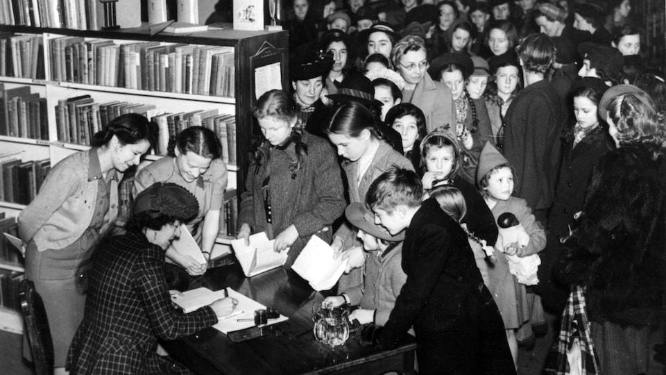 L'autrice est assise à une table et fait des signatures dans des livres. Une foule d'enfants est devant elle, parmi les bibliothèques de livres du magasin.