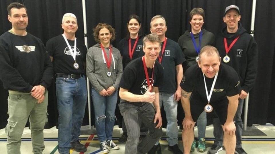 Neuf personnes posent dans un gymnase, huit d'entre eux portant une médaille au cou.