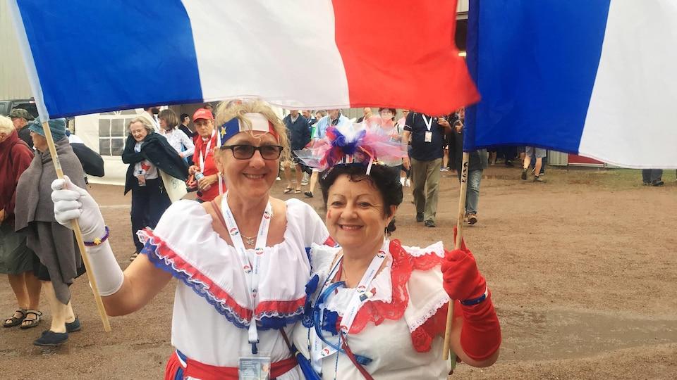 Deux femmes costumées brandissent des drapeaux de l'Acadie.