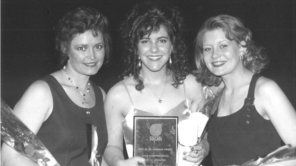 Trois femmes tiennent le prix de la SOCAN.