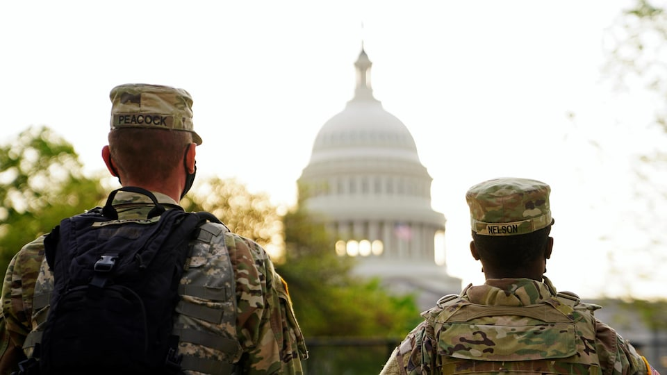 Two members of the National Guard, from behind, look at the Capitol.
