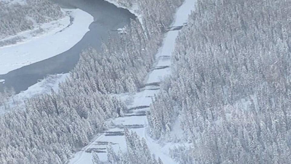 Une route enneigée près d'une rivière, des dizaines d'arbres sont couchés au travers de la chaussée.