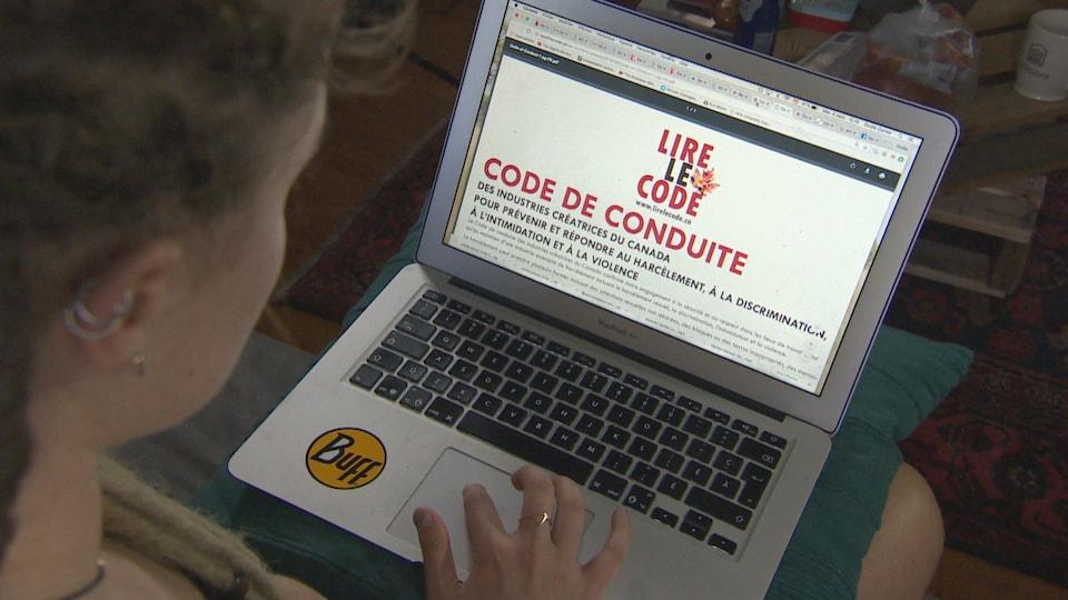 Une femme lit le code de conduite qui apparait à l'écran de son ordinateur portable.