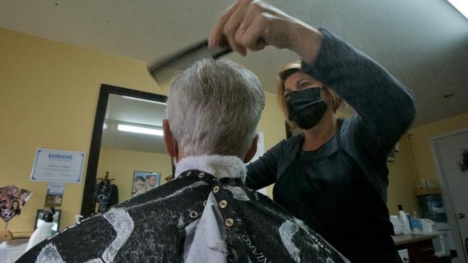 Une coiffeuse portant un masque coupe les cheveux d'un homme.