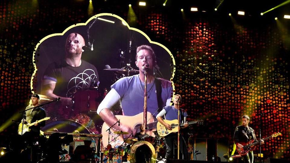 Les membres du groupe Coldplay chantent et jouent sur scène.
