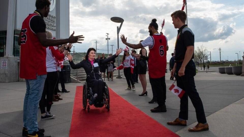 Colette Bourgonje avance sur un tapis rouge en fauteuil roulant pendant que des supporteurs la saluent.