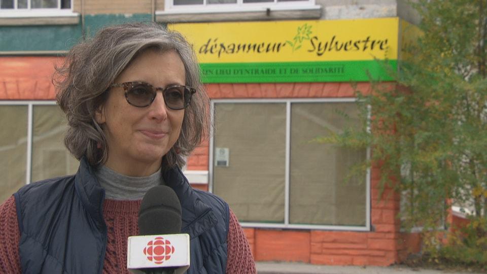 Une femme en entrevue avec Radio-Canada, devant l'immeuble où logeait le Dépanneur Sylvestre.