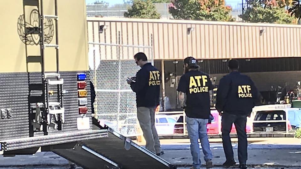 Des agents de l'ATF derrière un camion.