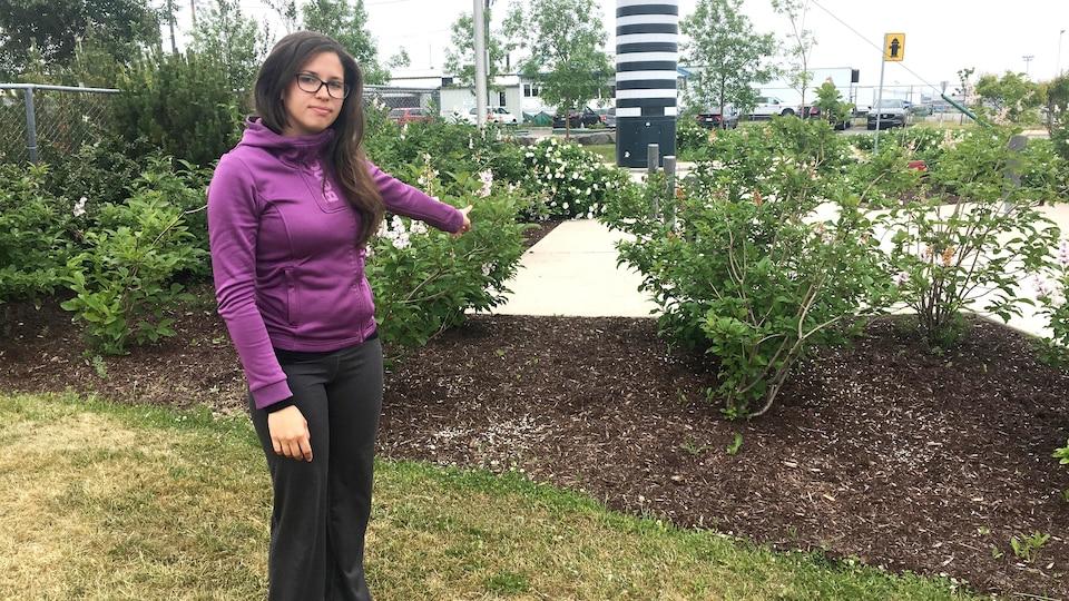 La préposée à l'accueil pour Les Croisières du Capitaine, Aurélie Royer, pointe l'endroit où la valise suspecte a été repérée samedi entre deux buissons.