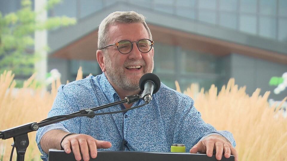 Régis Labeaume en train de rigoler derrière un pupitre et un micro lors d'une conférence de presse en extérieur.