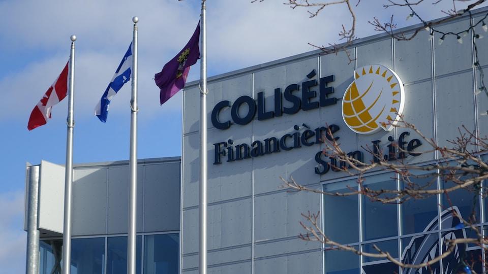 L'enseigne du Colisée Financière Sun Life avec des drapeaux flottant sous un ciel bleu.