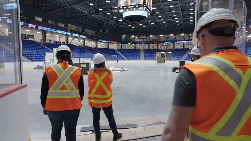 Des personnes en veste orange portent un casque de construction.
