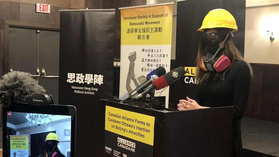 Cherie Wong porte un casque, un masque à gaz et des lunettes de protection en s'adressant aux journalistes.