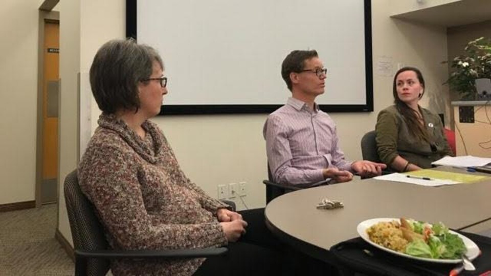 Trois personnes assises dans une salle avec un tableau à l'arrière plan.